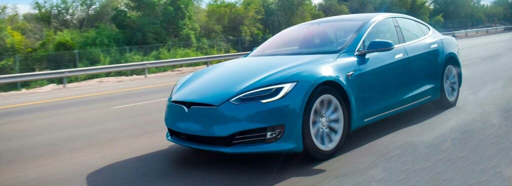 Picture of a blue Tesla on a highway