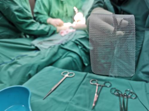 A surgeon prepping hernia mesh for an operation on a sterile table.
