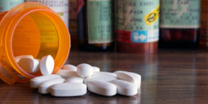 Opioids spilling out prescription bottle.