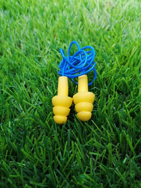 A pair of 3M earplugs on a field of grass.
