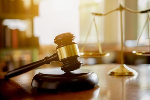 A gavel and scales of justice on a judge's podium.