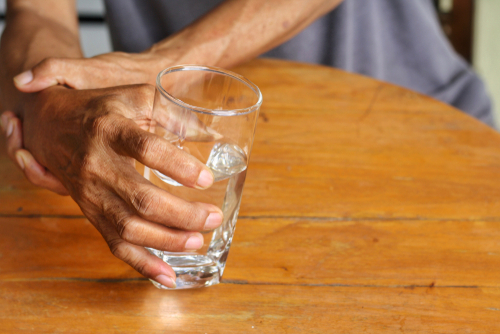 This is an image of a man holding a glass and using one hand to steady his shaking hand as a result of paraquat caused Parkinson's disease.